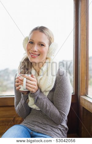 Portrait of a smiling young woman wearing earmuff with coffee cup sitting against cabin window