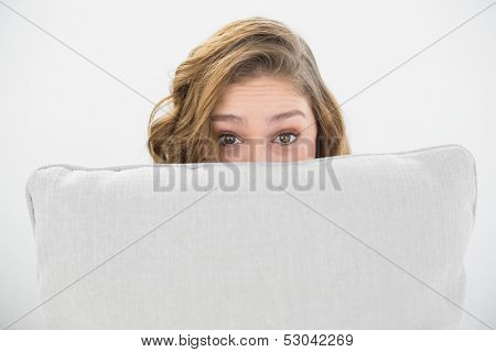 Astonished brunette woman hiding her face behind a white pillow looking at camera