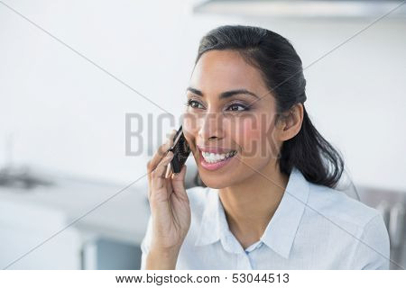 Gleeful young woman phoning with her smartphone standing in bright kitchen