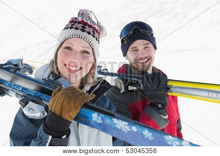 Close-up portrait of a smiling couple with ski boards standing on snow covered landscape