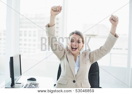 Happy cheering woman raising her arms sitting on her swivel chair looking at camera