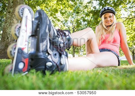 Casual attractive blonde wearing roller blades and helmet in a park