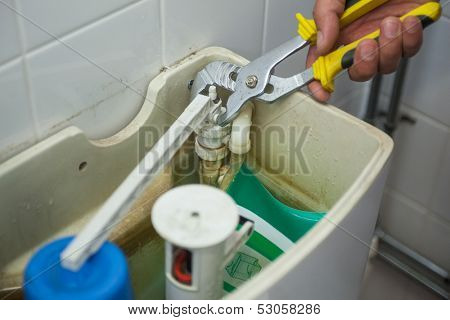 Close up of hand repairing toilet with pliers