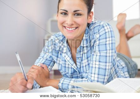 Portrait of beautiful young student doing assignments lying on the floor in the living room