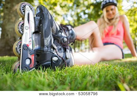 Casual attractive blonde wearing roller blades in a park