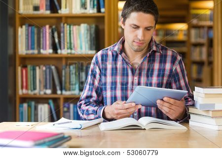 Concentrated mature male student using tablet PC at desk in the library