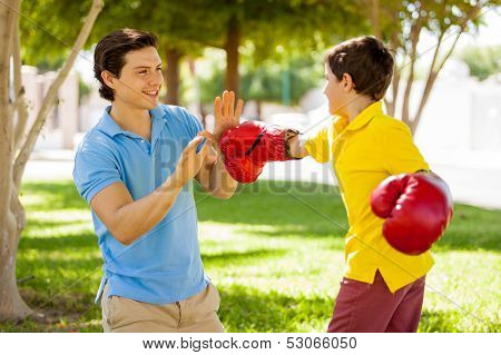 Father and son boxing outdoors