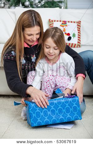 Mother and daughter opening Christmas present at home