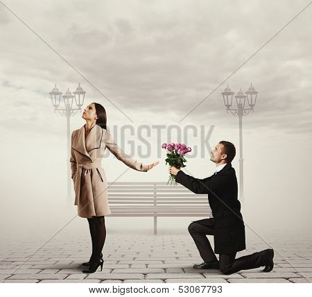 angry young woman rejecting man with flowers
