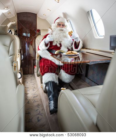 Man in Santa costume having cookies and milk in private jet
