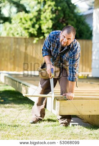 Full length portrait of confident mid adult worker cutting wood with saw at construction site