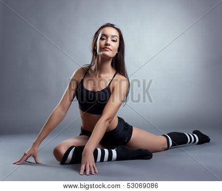 Graceful slender woman sitting on split in studio