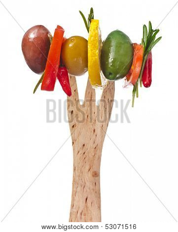 Wooden fork with colored olives and herb spice with copy space isolated on a white background