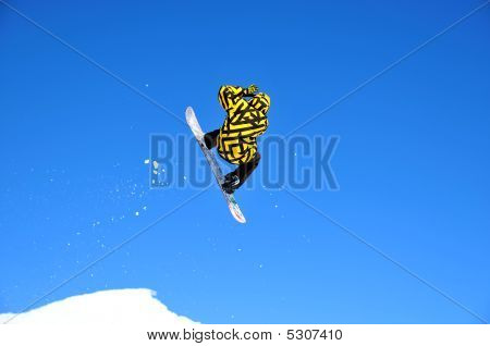Snowboarder In Black And Yellow  Jumping