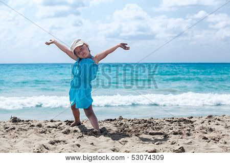 Joyous Young Girl With Hands Up Relaxing On Sandy Beach. Copyspace