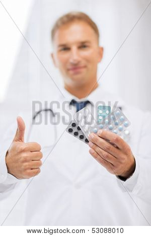 healthcare, medical and pharmacy concept - male doctor with packs of pills showing thumbs up