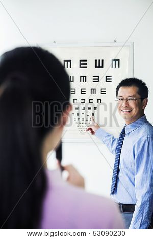 Optometrist administering eye exam on eye chart