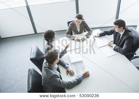 Four business people sitting around a table and having a business meeting