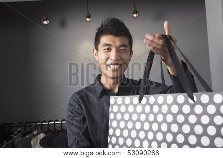 Store clerk holding shopping bag at fashion store