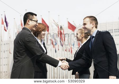 Four smiling business people meeting and shaking hands