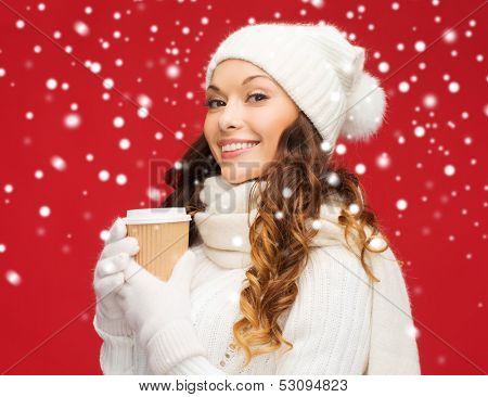 winter, people, happiness, drink and fast food concept - woman in hat with takeaway tea or coffee cup