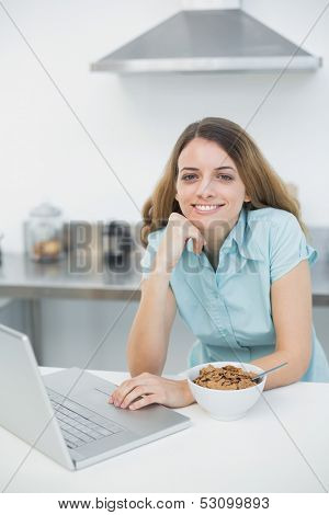 Gleeful woman using her laptop smiling at camera having prepared a bowl with cereals