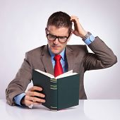 picture of scratching head  - pensive young business man reding a book and scratching his head - JPG