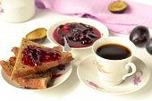 Toast with plum jam and coffee for breakfast