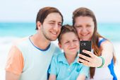 Beautiful family at beach making a self portrait with mobile phone