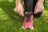 Close up of sporty woman tying her shoelaces kneeling on a lawn