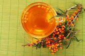 stock photo of sea-buckthorn  - Branches of sea buckthorn with tea on bamboo background - JPG