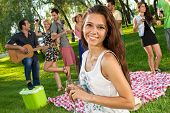 stock photo of vivacious  - Beautiful vivacious girl enjoying a glass of red wine while partying with her college friends in a lush green park during their summer vacation - JPG