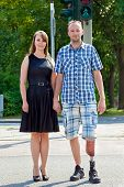 stock photo of amputee  - Confident handicapped man wearing an artificial limb having had one leg amputated standing hand in hand with an attractive woman in a street - JPG