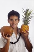 stock photo of kukui nut  - Hawaiian man wearing a kukui nut lei holds a pineapple and a coconut - JPG
