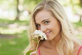 image of girly  - Beautiful blonde woman smelling a flower sitting in a park smiling at camera - JPG