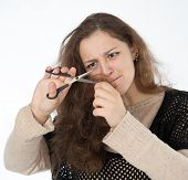 picture of split ends  - woman mows split ends of hair with scissors - JPG
