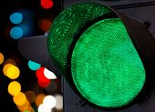 stock photo of traffic signal  - Green traffic light with colorful unfocused lights on a background - JPG