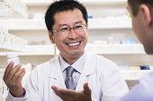 picture of prescription  - Smiling pharmacist showing prescription medication to customer - JPG