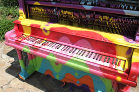 stock photo of rainbow piano  - Colorfully decorated old piano stands outside in a park  - JPG