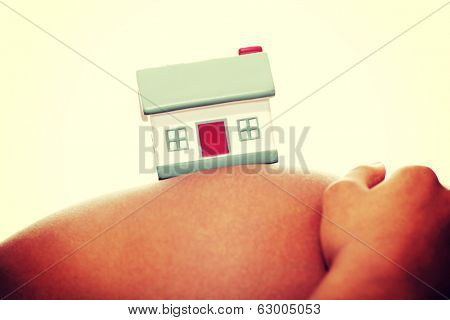 Close-up of pregnant woman touching her belly with toy house on it