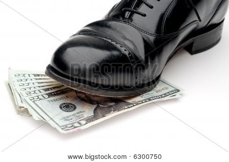 Horizontal Image Of A Black Leather Shoe Standing On A Pile Of Money
