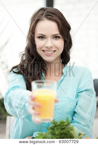health and beauty concept - young woman holding glass of orange juice