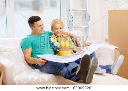 moving, home and couple concept - smiling couple relaxing on sofa and looking at blueprint in new home