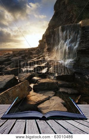 Book Concept Beautiful Landscape Image Waterfall Flowing Into Rocks On Beach At Sunset