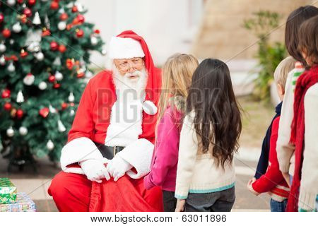 Santa Claus looking at children standing in a queue outdoors