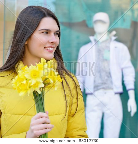Portrait of young beautiful woman with sping flowers, outdoor over shopwindow with dummy.