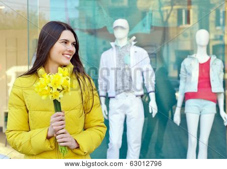 Portrait of young beautiful woman with spring flowers, outdoor over shopwindow with dummy.