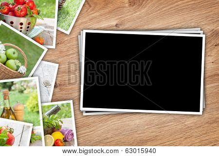 Stack of printed pictures collage on wooden table with copy space for your photo