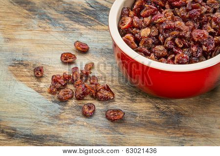 dried cranberries in a stoneware bowl on a grunge painted wood background