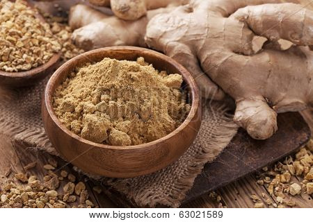 Ginger fresh root and ginger spice on a wooden table